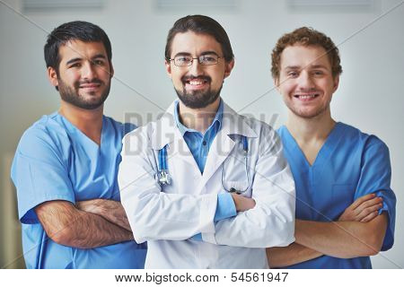Portrait of three clinicians in uniform looking at camera with smiles