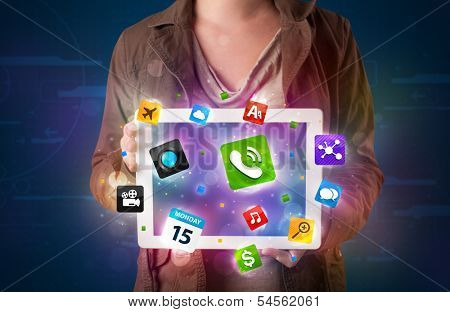 Young lady holding a tablet with modern colorful apps and icons