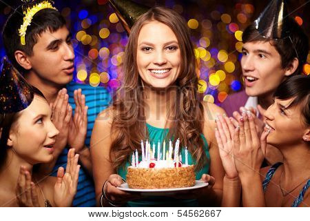 Portrait of joyful girl holding birthday cake with friends near by at party