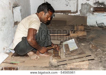 Man Punches Manually Holes In Carton Guide For Hand Loom.