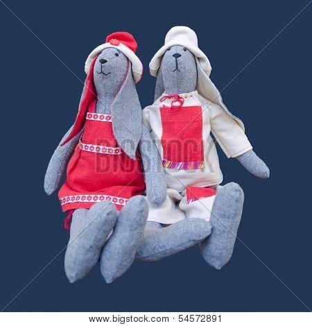 Isolated Handmade Dolls Bunny Family In Homespun Clothing Sitting