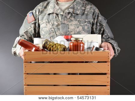 Closeup of a soldier in fatigues holding a wooden box full of canned and packaged food for a holiday charity drive. Horizontal format man is unrecognizable.