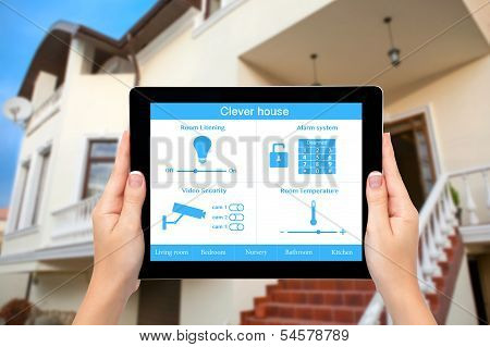 Female Hands Hold A Tablet With System Clever House On The Background Of The House