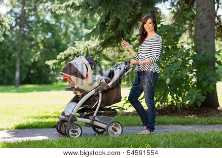 Portrait of happy young mother with cell phone and baby carriage walking in park