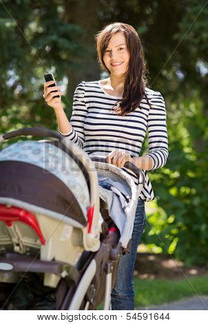 Portrait of beautiful young woman with baby carriage using cell phone in park