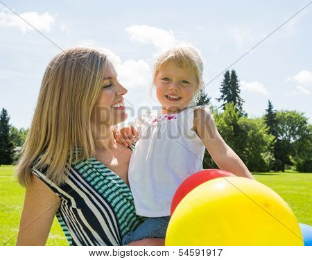 Happy mid adult mother and daughter with helium balloons in park