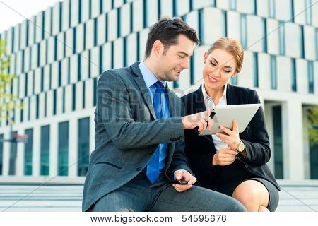 business people or businessman and businesswoman working outdoor, using pad or tablet computer and mobile cell phone