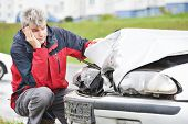 stock photo of wrecking  - Adult upset driver man inspecting automobile body after crash car collision accident - JPG
