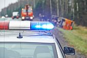 stock photo of lorries  - police car with a flasher in front of damaged lorry trailer in ditch of highway - JPG