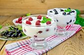 stock photo of yogurt  - Thick yogurt in two glasses with raspberry and black currant on a napkin berries and mint on a wooden boards background - JPG
