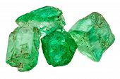 stock photo of uncut  - Four rich green uncut emerald crystals on white - JPG