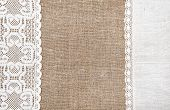 stock photo of sackcloth  - Burlap background with white lacy and linen cloth - JPG