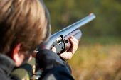 stock photo of gun shot  - Shooter takes aim for a shot from rifle