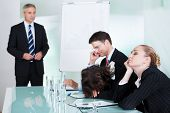 stock photo of boring  - Bored businesswoman sleeping in a meeting as her colleague who is giving the presentation talks in the background