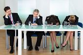 stock photo of sleepy  - Bored panel of professional judges or corporate interviewers lounging around on a table napping as they wait for something to happen - JPG