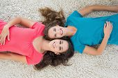 pic of slumber party  - High angle portrait of two young female friends lying on rug in the living room at home - JPG