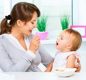 picture of child feeding  - Mother Feeding Her Baby Girl with a Spoon - JPG