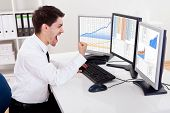 stock photo of trade  - Over the shoulder view of the computer screens of a stock broker trading in a bull market showing ascending graphs - JPG
