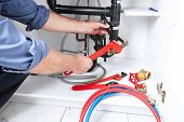 image of clog  - Hands of professional Plumber with a wrench - JPG