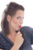 stock photo of titillation  - Young woman flirting holding a lollipop to her lips - JPG