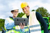 stock photo of bulldozer  - Construction worker and engineer on site discussing blueprints on pad or tablet computer - JPG