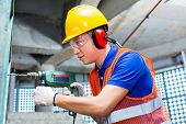 Asian Indonesian builder or worker drilling with a machine or drill, ear protection and hardhat or h