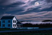 stock photo of moonlit  - white house with picket fence on a moonlit night in the countryside - JPG
