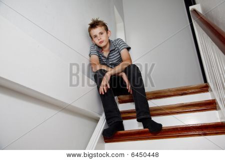 Boy Sitting On The Staircase Looking Sad