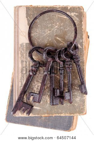 Old keys on old books isolated on white