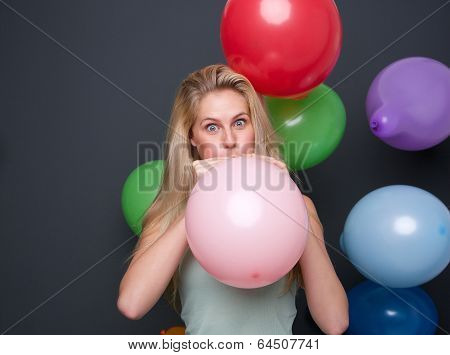 Blond Woman Inflating Balloons For A Party
