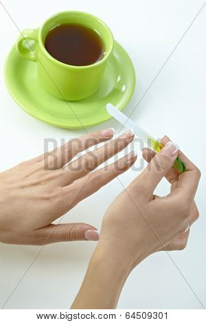 Female hand filing nails over cup of tea. White background, cosmetics.