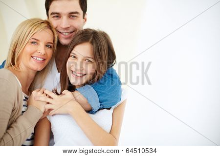 Portrait of joyful family looking at camera with smiles in isolation