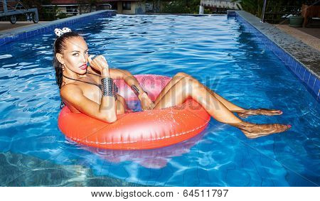 Woman Floating In Inner Tube In Pool And Having Fun
