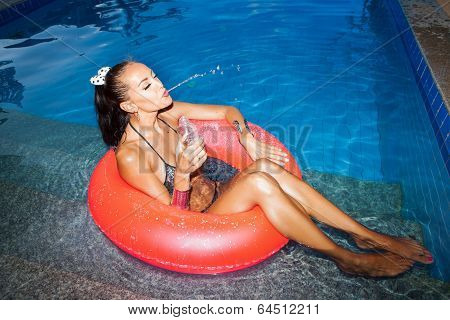 Woman Floating In Inner Tube In Pool And Drinking Water