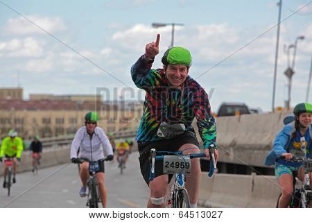 Green hatted rider gestures happily