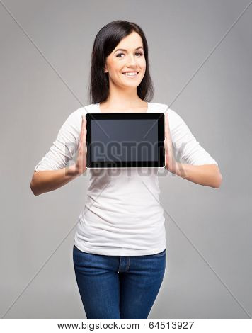 Young and beautiful teenager girl holding an ipad tablet pc in her arms over grey background