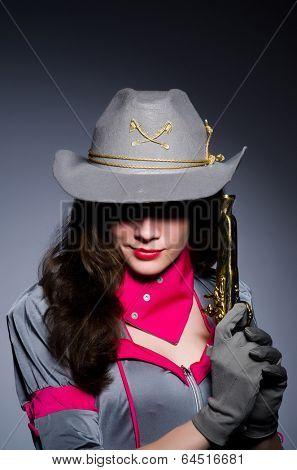 Woman cowgirl with gun in studio