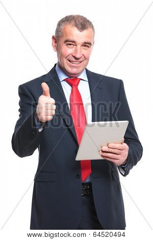 mid aged business man showing the thumb up sign while holding a tablet and smiling. isolated on a white background