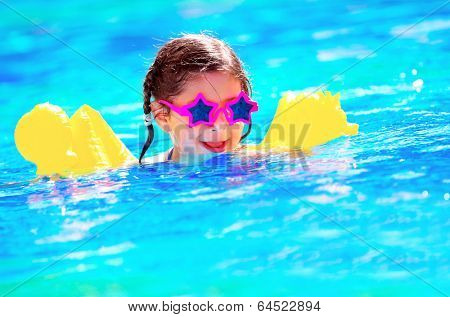 Cute little baby swimming in the pool, wearing funny sunglasses, enjoying summer weekend in aquapark, holidays and vacation concept