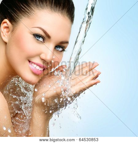Beautiful Model Woman with splashes of water in her hands. Beautiful Smiling girl under splash of water with fresh skin over blue background. Skin care, Cleansing and moisturizing concept. Beauty face