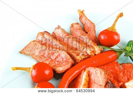 bacon meat slices served with tomatoes capers and red hot chili peppers on blue plate isolated on white background