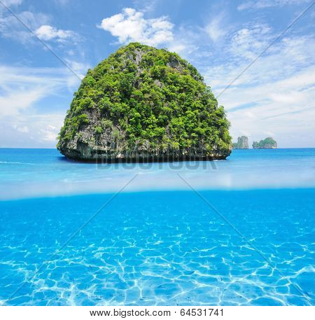 Beautiful uninhabited island in Thailand with white sand bottom underwater and above water split view