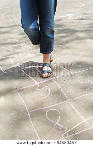 Girl Hoping In Hopscotch Outdoors