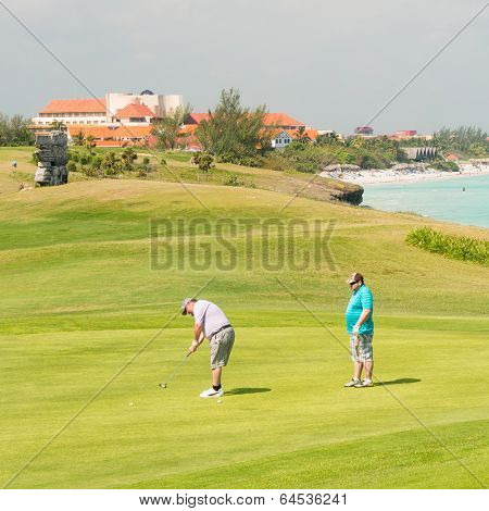 VARADERO,CUBA - APRIL 26,2014: Competitors playing at the Varadero Golf Club on a beautiful sunny day with the beach on the background