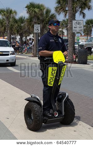 JACKSONVILLE BEACH, FL - APRIL 27, 2014: A police officer on a Segway during the 68th annual Opening of the Beaches Parade. Using Segways, police are able to patrol large areas three times faster.