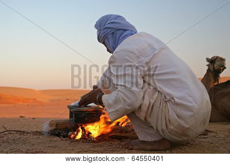 Native arab bedouin making a dinner in middle of the desert in Egypt