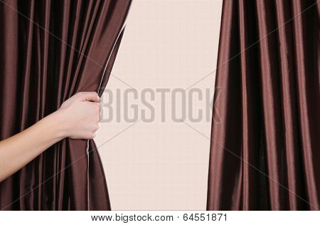 Hand opening curtain on beige background