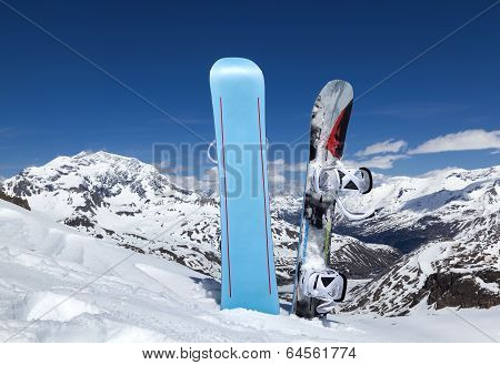 Two Snowboard Standing Upright In Snow