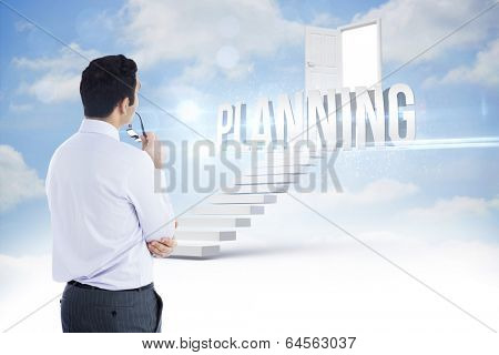 The word planning and businessman holding glasses against steps leading to open door in the sky