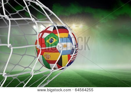 Football in multi national colours at back of net against football pitch under green sky and spotlights